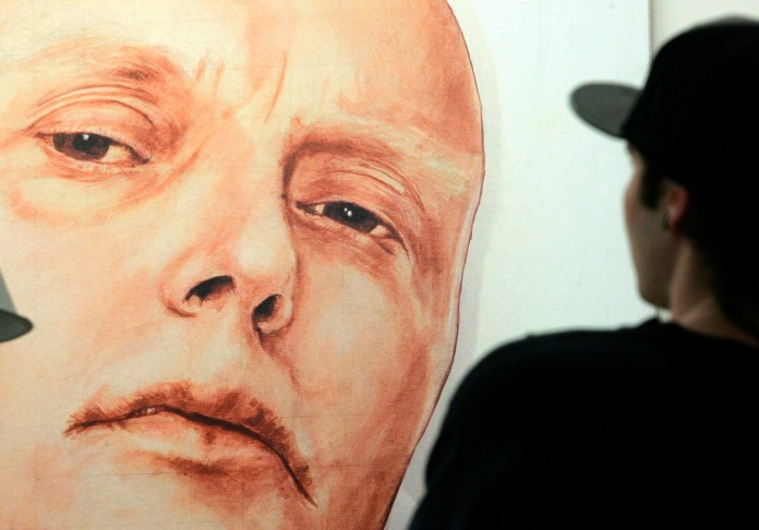 A man looks at a portrait of ex-spy Andrei Litvinenko by Russian artists Dmitry Vrubel and Viktoria Timofeyeva in the Marat Guelman gallery in Moscow May 22, 2007. Moscow cannot extradite former KGB agent Andrei Lugovoy to Britain on charges of murdering fellow ex-spy Alexander Litvinenko because of a constitutional ban, the Russian Prosecutor-General's office said on Tuesday. REUTERS/Sergei Karpukhin (RUSSIA) - RTR1PYPQ